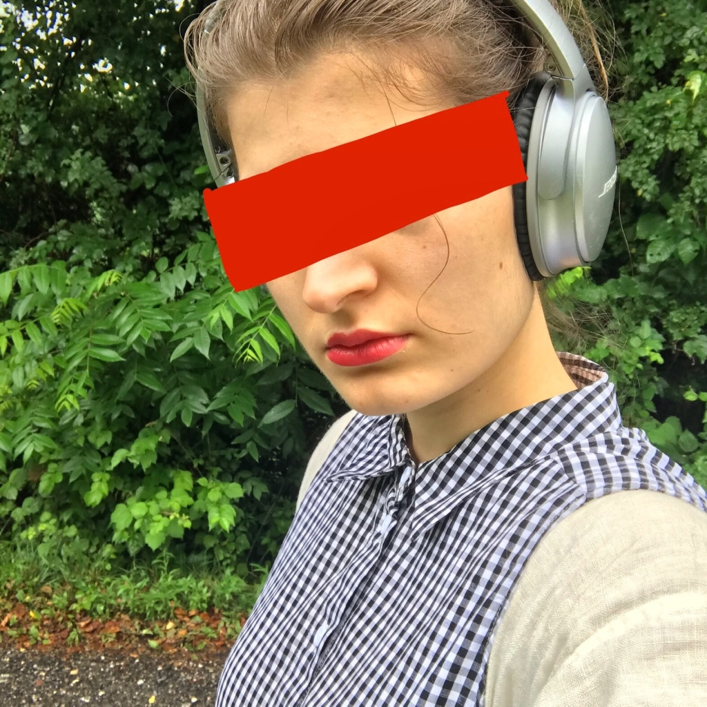 The author is a fair-skinned person wearing headphones.  Their lips are painted red, and their eyes are covered by a big red block to obscure their identity.  They are wearing a white long sleeved shirt underneath a black and white gingham collared, sleeveless button down that is fully buttoned.  They stand against a backdrop of green leaves.